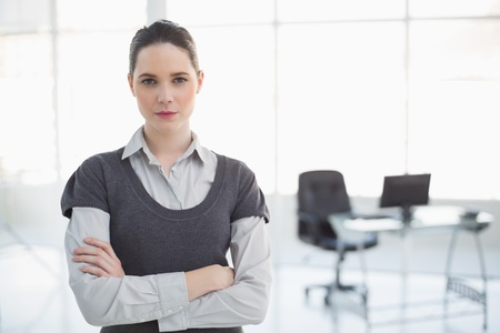 Stern businesswoman posing in bright office photo