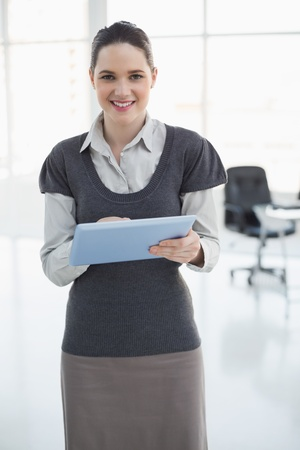 Cheerful businesswoman holding tablet pc in bright office photo