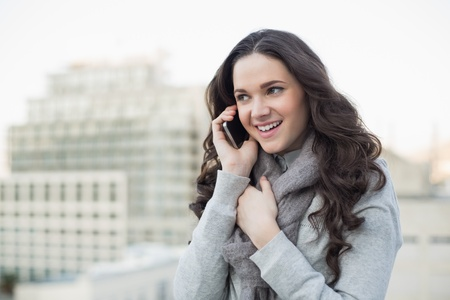 Cheerful pretty brunette in winter clothes having phone call outside on a cloudy day photo