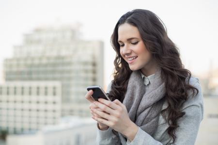Fröhlich hübsche Brünette in Winterkleidung Senden einer SMS auf ihrem Smartphone draußen auf einem bewölkten Tag Lizenzfreie Bilder