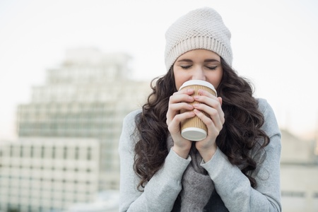 Pretty young brunette drinking coffee outside on a cloudy day photo