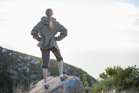 adventuring: Rear view of blonde woman standing on stone in the countryside Stock Photo