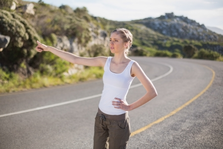 Stranded woman hitching a lift on a deserted country road Stock Photo