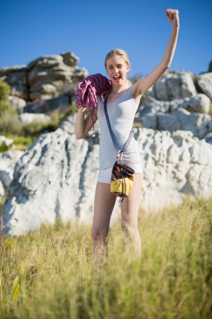 Woman holding climbing equipment and showing muscle looking at camera photo
