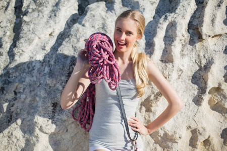 Smiling woman holding climbing equipment leaning at rock looking at camera photo