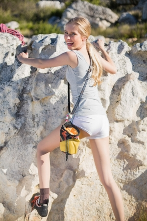 Rear view of blonde active woman climbing smiling back at camera photo