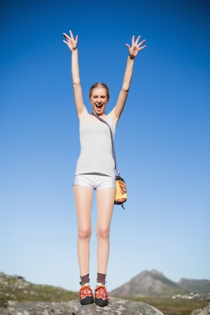 Active woman standing on rock cheering on a sunny day in the country Stock Photo