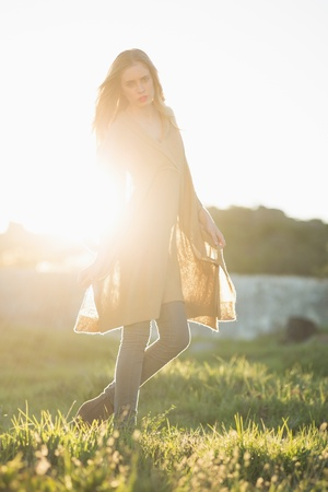 Attractive woman posing in a poncho in the sunshine photo