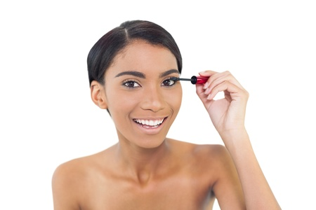Pretty natural model applying mascara while posing on white background photo