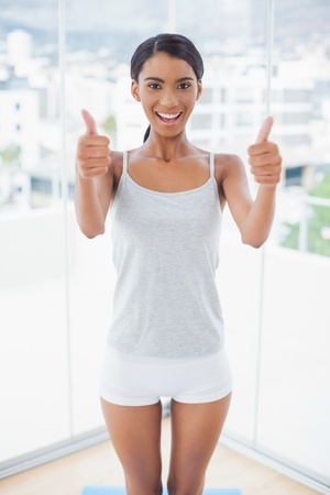 Attractive model in sportswear giving thumbs up to camera in bright room at home Stock Photo - 21770764
