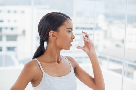 Pretty model using her asthma atomizer after exercising photo