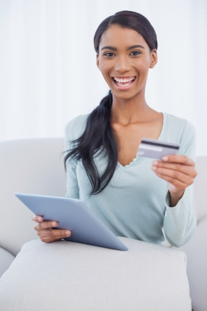 Smiling attractive woman in bright living room using her tablet pc to buy online photo