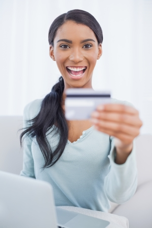 Smiling pretty woman in bright living room using her laptop to buy online photo