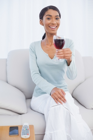 Smiling attractive woman holding glass of red wine sitting on cosy sofa photo