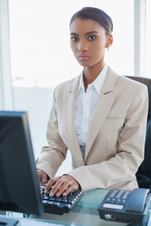 unsmiling: Serious businesswoman working on her computer in bright office Stock Photo