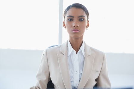 unsmiling: Serious elegant businesswoman posing in bright office Stock Photo