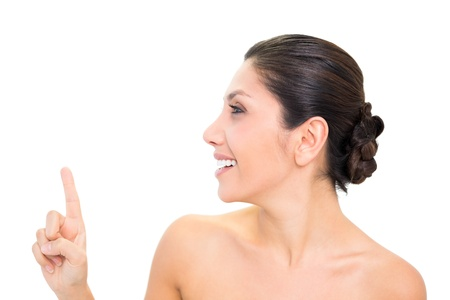 Smiling brunette pointing up with one hand with head turned on white background photo