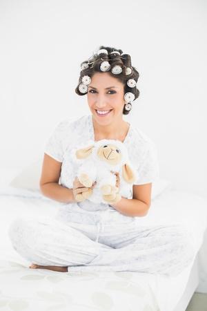 hair rollers: Morena en rulos sostienen ovejas de peluche sonriendo a la c�mara en casa en el dormitorio