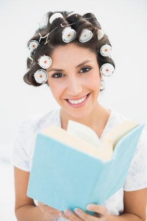hair rollers: Morena sonriente en los rodillos del pelo que sostienen un libro en la cama en su casa en el dormitorio Foto de archivo