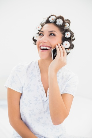 Laughing brunette in hair rollers on the phone on bed at home in bedroom photo