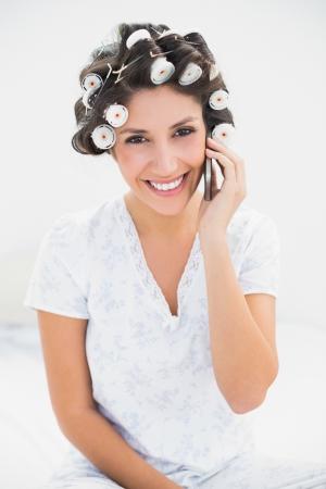 hair rollers: Pretty morena en rodillos de pelo en el tel�fono en la cama en su casa en el dormitorio Foto de archivo