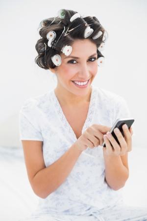 hair rollers: Pretty morena en rulos con smartphone en la cama mirando a la c�mara en casa en el dormitorio
