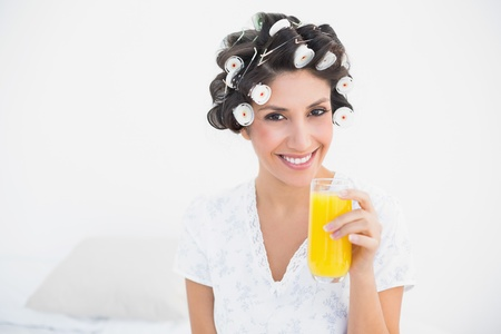 Pretty brunette in hair rollers holding glass of orange juice smiling at camera at home in bedroom photo