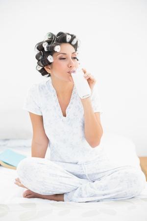 hair rollers: Pretty morena en rulos vaso de leche de consumo en el hogar en el dormitorio