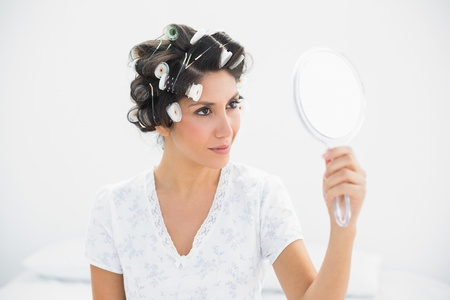 Happy brunette in hair rollers holding hand mirror at home in bedroom photo