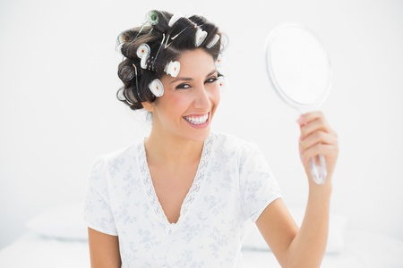 Happy brunette in hair rollers holding hand mirror smiling at camera at home in bedroom photo