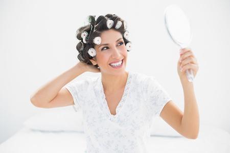 Happy brunette in hair rollers looking in hand mirror at home in bedroom