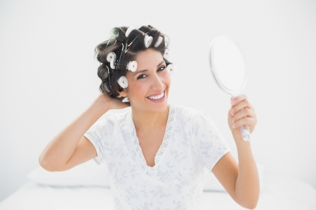 Smiling brunette in hair rollers holding hand mirror at home in bedroom