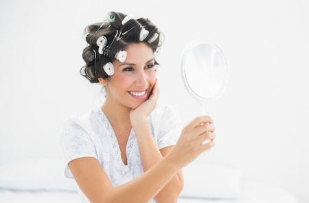 hair rollers: Morena sonriente en los rodillos del pelo mirando en el espejo de mano en el hogar en el dormitorio Foto de archivo