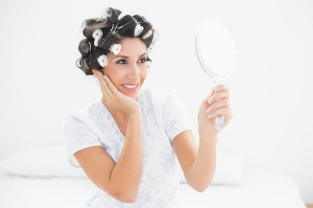 Pretty brunette in hair rollers looking in hand mirror at home in bedroom Stock Photo