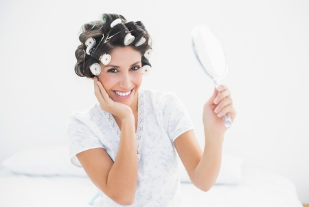 Pretty brunette in hair rollers holding hand mirrorat home in bedroom photo
