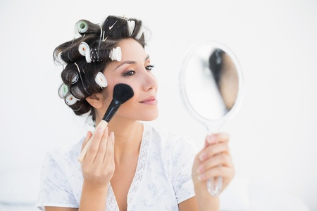 Pretty brunette in hair rollers holding hand mirror and applying makeup at home in bedroom photo