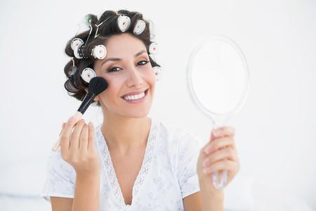 hair rollers: Morena sonriente en los rodillos del pelo sosteniendo espejo de mano y la aplicaci�n de maquillaje en su casa en el dormitorio Foto de archivo