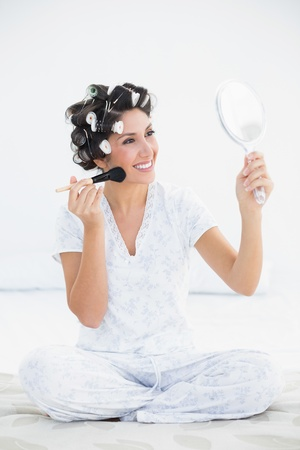 Cheerful brunette in hair rollers holding hand mirror and applying makeup at home in bedroom photo