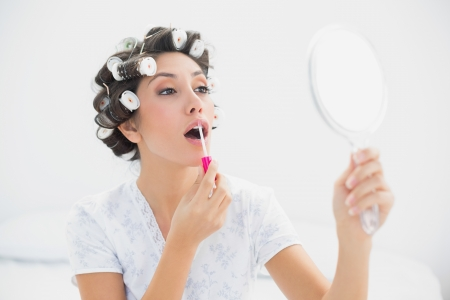 Pretty brunette in hair rollers holding hand mirror and applying lip gloss at home in bedroom photo