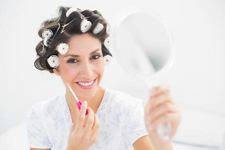 hair rollers: Brunette feliz en los rodillos del pelo que sostienen la mano espejo y brillo de labios en su casa en el dormitorio
