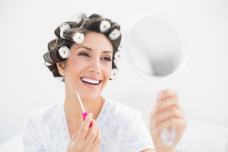 Happy brunette in hair rollers looking in hand mirror and holding  lip gloss at home in bedroom photo