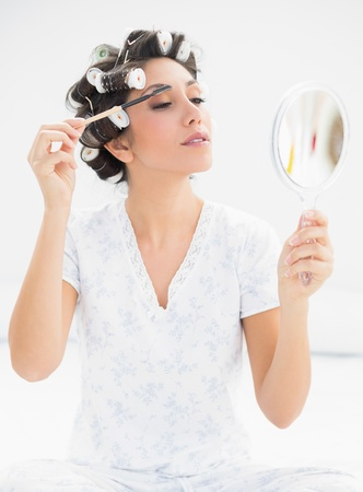 Happy brunette in hair rollers looking in hand mirror and brushing her eyebrows at home in bedroom photo