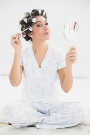 Happy brunette in hair rollers holding hand mirror and brushing her eyebrows at home in bedroom photo
