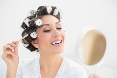 hair rollers: Morena sonriente en los rodillos del pelo mirando en el espejo de mano y cepillar las cejas en casa en el dormitorio