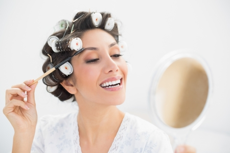 Smiling brunette in hair rollers looking in hand mirror and brushing her eyebrows at home in bedroom photo