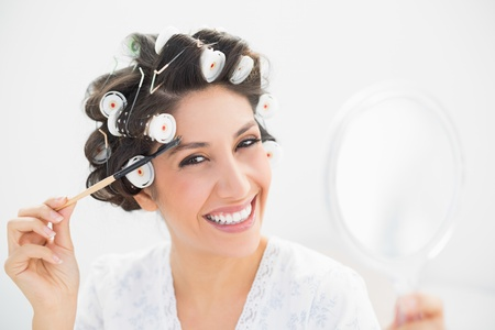 Pretty brunette in hair rollers holding hand mirror and brushing her eyebrows in bedroom at home photo