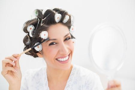 hair rollers: Pretty morena en rulos celebraci�n espejo de mano y cepillar las cejas en el dormitorio en casa Foto de archivo