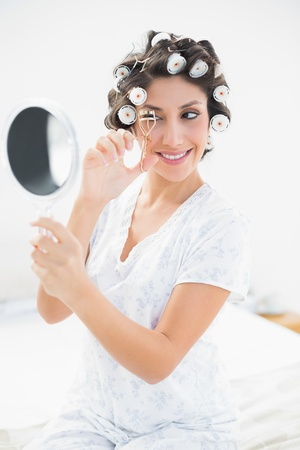 Pretty brunette in hair rollers looking in hand mirror and using eyelash curler in bedroom at home photo