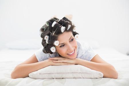 hair rollers: Pretty morena en rulos acostado en su cama en el dormitorio en casa