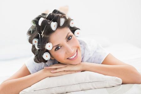 hair rollers: Pretty morena en rulos acostado en la cama sonriendo a la c�mara en el dormitorio en casa